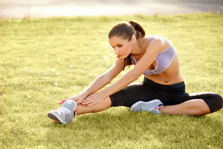 dynamic activity: Portrait of Young Sporty Woman Doing Stretching Exercise Stock Photo