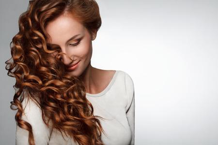 hair curly: Mujer hermosa con el pelo rizado largo