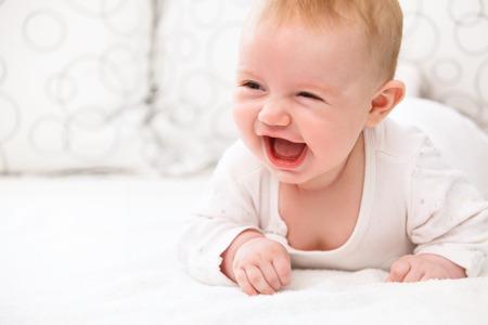 ベッドで横になっている笑顔の赤ちゃん女の子