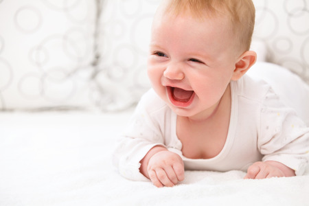 Smiling Baby Girl Lying in the Bed Archivio Fotografico