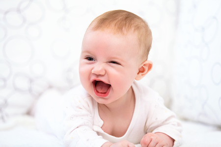 baby bed: Smiling Baby Girl Lying in the Bed Stock Photo