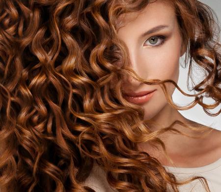 美しさ: 長い巻き毛を持つ美しい若い女性