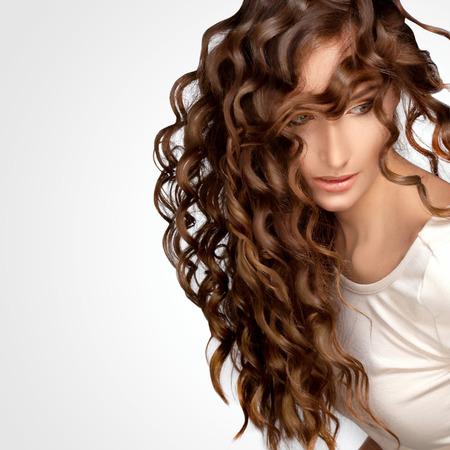 cabello rizado: Mujer hermosa con el pelo rizado largo