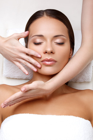 dayspa: Face Massage. Close-up of a Young Woman Getting Spa Treatment.