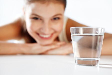 Lachende jonge vrouw met een glas water Stockfoto