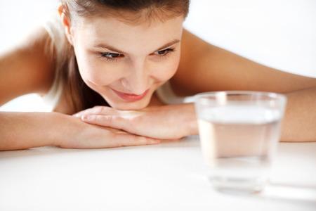 personas tomando agua: Mujer joven sonriente con un vaso de agua