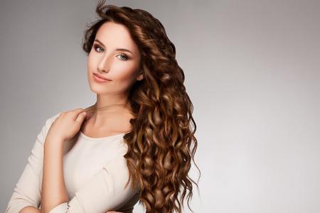 peluqueria: Mujer hermosa con el pelo rizado largo.