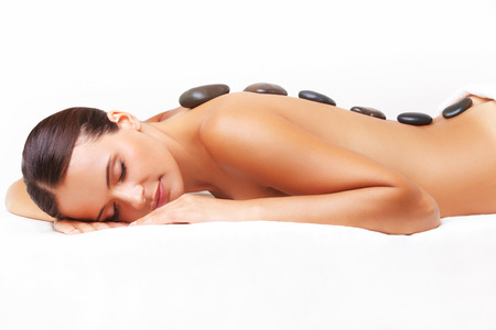 spa and resort: Beautiful Woman Getting Spa Hot Stones Massage in Spa Salon.