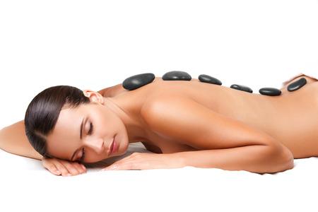 massage: Beautiful Woman Obtenir Spa massage aux pierres chaudes dans le Salon Spa. Banque d'images