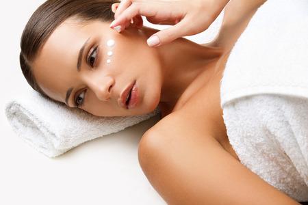 masaje facial: Mujer hermosa que consigue Tratamiento de spa, crema cosm�tica en una mejilla