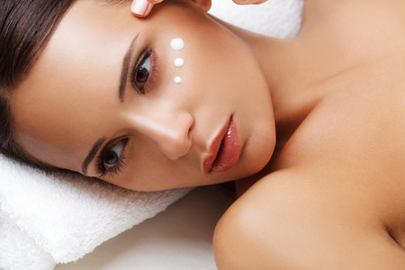 woman face cream: Close-up of a Young Woman Getting Spa Treatment, Cosmetic Cream on a Cheek Stock Photo