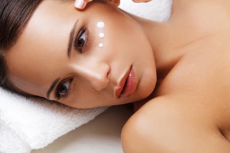 Close-up von einer jungen Frau immer Spa-Behandlung, kosmetische Sahne auf einer Wange