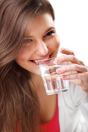 水のガラスと笑顔の若い女性