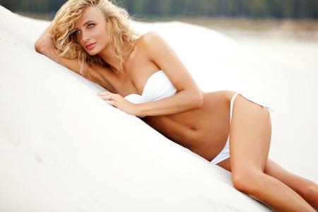 flaco: Mujer joven, hermosa, deportivo y sexy tumbado en la playa