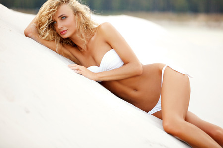 Young, beautiful, sporty and sexy woman lying on the beach