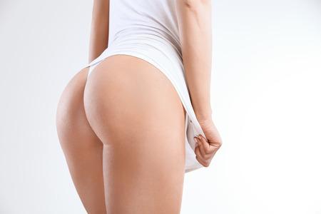 Primer plano de una mujer hermosa que muestra perfecta de glúteos en el blanco