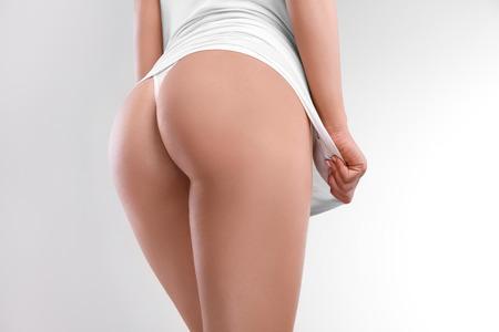nalga: Primer plano de una mujer hermosa que muestra perfecta de glúteos en el blanco