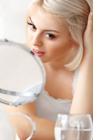 mirror face: Beautiful Woman Looking at Her Face in the Mirror Stock Photo