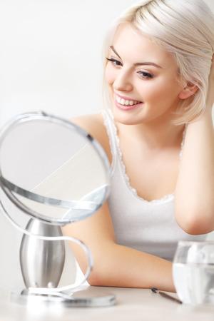 mujer maquillandose: Mujer hermosa que mira a la cara en el espejo Foto de archivo
