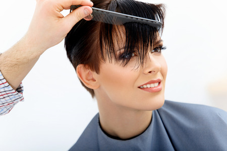 horizontal haircut: Brown Hair. Hairdresser doing Hairstyle. Beauty Model Woman. Haircut. Hair care