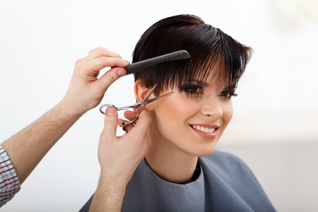 Hairdresser doing Hairstyle. Brunette with Short Hair in Hair Salon. Haircut. Hair care