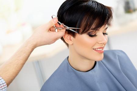 헤어. 뷰티 살롱에서 여자의 머리를 절단하는 미용사. 헤어 스타일
