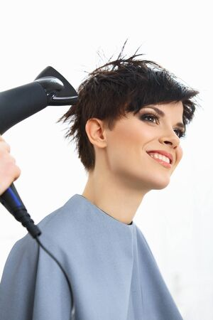 Hairdresser Using Dryer on Woman Wet Hair in Salon.  Short Hair. Hairstyle