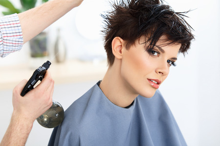 girl short hair: Brown Hair. The Hairdresser doing Hairstyle in Hair Salon. Haircut.