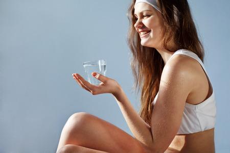 tomando refresco: Retrato de mujer joven con un vaso de agua Foto de archivo