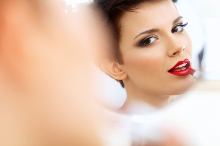 lip stick: Close up Portrait of Young Woman With Red Lips. Beautiful Woman Doing Daily Makeup. Lipstick applying Stock Photo