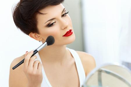 mujer maquillandose: Muchacha de la belleza con el cepillo del maquillaje. Maquillaje Natural para Mujer Morena con labios rojos. Hermoso Rostro. Aplica maquillaje Foto de archivo