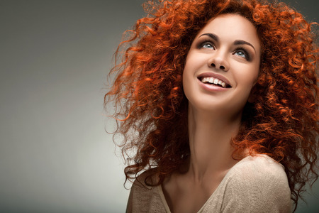 long curly hair: Red Hair. Beautiful Woman with Curly Long Hair. Stock Photo