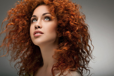 salon background: Red Hair. Beautiful Woman with Curly Long Hair. Stock Photo