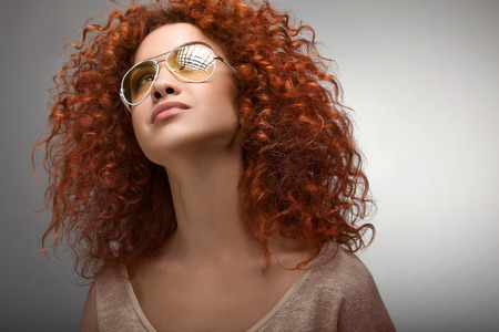 Red Hair. Beautiful Woman with Curly Long Hair and Sunglases Archivio Fotografico