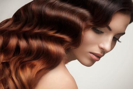 cabello rizado: Pelo Castaño. Retrato de la mujer hermosa con el pelo ondulado largo. Imagen de alta calidad. Foto de archivo