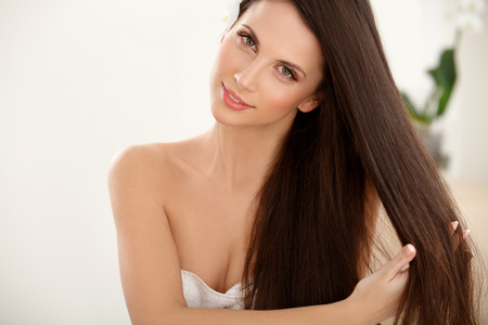 haircare: Brown Hair. Beautiful Brunette with long Hair. Smiling Girl Isolated on a White Background. Haircare