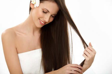 Brown Hair. Beautiful Brunette with long Hair. Smiling Girl Isolated on a White Background. Haircare