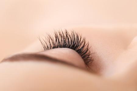 cerrar: Mujer de ojos con largas pestañas. Extensión de la pestaña