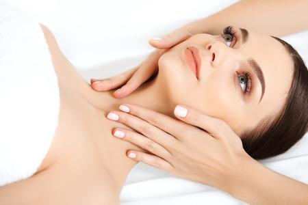 masajes faciales: Masaje de cara. Primer plano de una mujer joven que consigue Tratamiento de spa. Foto de archivo