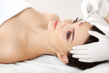 inyeccion: Hermosa mujer obtiene inyección En Su Rostro. Cirugía Cosmética