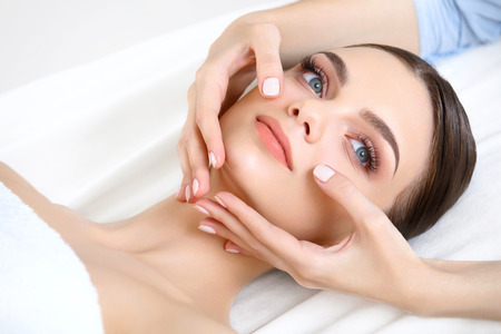 Face Massage. Close-up of a Young Woman Getting Spa Treatment. photo