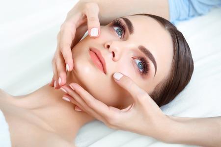 tratamientos corporales: Masaje de cara. Primer plano de una mujer joven que consigue Tratamiento de spa. Foto de archivo