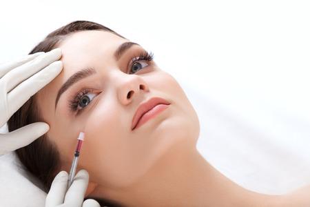 arrugas: Hermosa mujer recibe inyecciones. Cosmetología. Cara de belleza