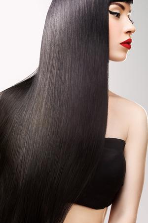 Zwart haar. Mooi Donkerbruin Meisje met Gezond Lang Haar. Rode lippen en mooie make-up. Stockfoto