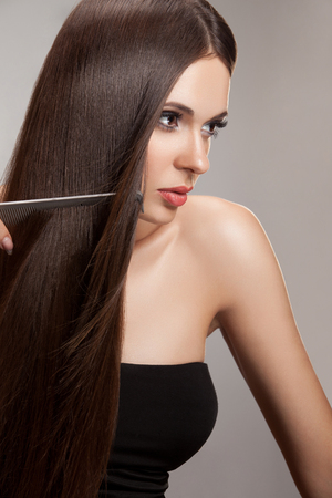 haircare: Beautiful Woman combs her Healthy Long Hair. High quality image.
