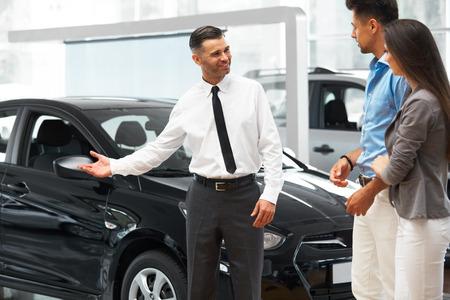 new automobiles: Ð¡ar Salesman Invites Customers at Showroom.