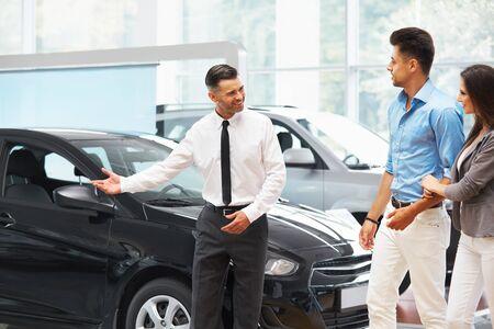 car sales: Ð¡ar Salesman Invites Customers at Showroom.