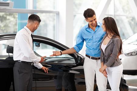 Exposición de coches. Pareja joven comprar un coche nuevo en la concesionaria. Foto de archivo - 45680346