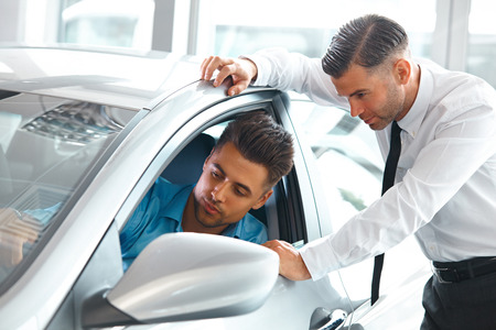 car dealers: Car Sales Consultant Showing a New Car to a Potential Buyer in Showroom