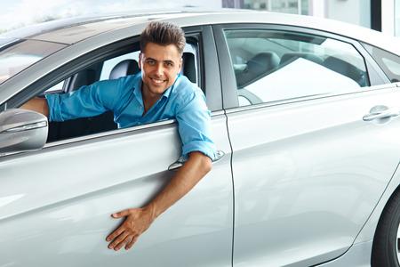 soñar carro: Car Showroom. Hombre feliz en el interior del coche de su sueño.